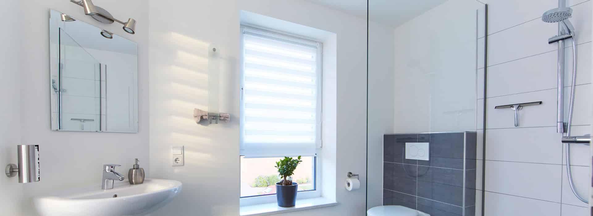 Das Badezimmer mit Dusche, Wc, Spiegelschrank über dem Waschbecken und einem Fenster.